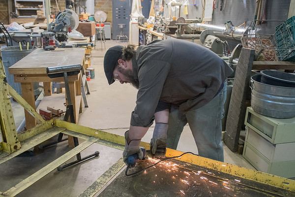 Rick Esser, president and shop manager of Mankato Makerspace, grinds off the welds of a piece of metal to be removed, leaving a large push cart for the organization. The cart will be used to move larger materials around the organization's warehouse space. Photo by Jackson Forderer