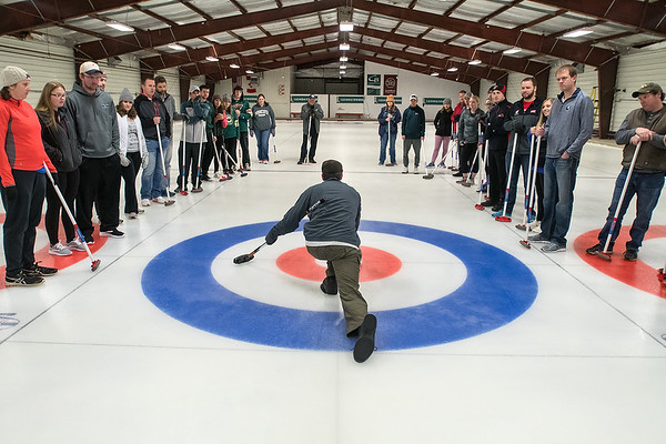 Joe Gangi (center) shows students at a Learn to Curl class how to slide off of the hack to deliver a rock on Friday. The Mankato Curling Club has added extra classes due to the popularity of curling rising after Mapleton-native John Landsteiner and the U.S. men's team took gold in Pyeong Chang. Photo by Jackson Forderer