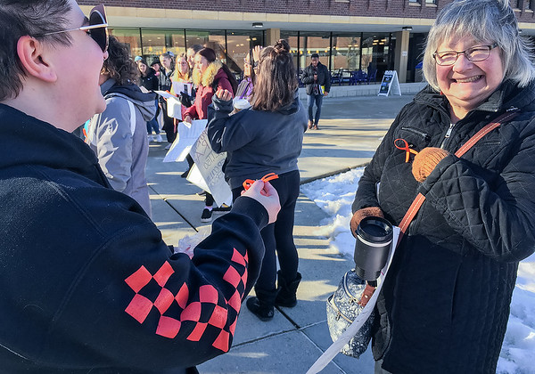 Tyler Quast (left), a student at Minnesota State, hands out an orange ribbon to Professor Barbara Carson (right), who points out she already received one, during a rally on campus Wednesday. Orange is the color used for gun violence awareness. Photo by Diana Rojo-Garcia