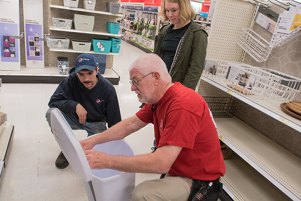 Target employee Ron Spreng (center) helps Alex Peters (left) and Autumn Olson with the foot petal mechanism to a garbage can lid on Thursday. Spreng, 69 years old, said that earning money is not his primary motive for working at Target, but rather to help him stay busy, keep a regular schedule and interact with people. Photo by Jackson Forderer
