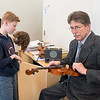 Orchestra teacher David Urness (right) tunes violins for seventh-graders before the start of class at Prairie Winds Middle School on March 9. Urness has taught orchestra at Mankato East, Prairie Winds and other area schools for the past 39 years and will retire at the end of this school year. Photo by Jackson Forderer