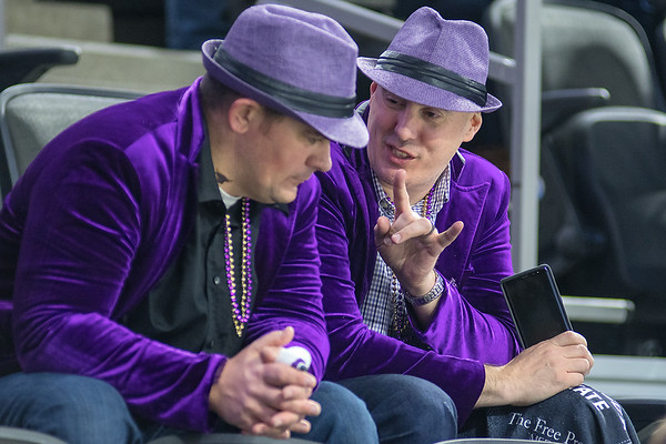Tony Smith (right) talks to Dan Hansen, both from Mankato, during the second intermission of the MSU men's hockey game played in Sioux Falls on Friday. The two were part of a larger group of seven who all wore purple jackets and hats for the game. Photo by Jackson Forderer