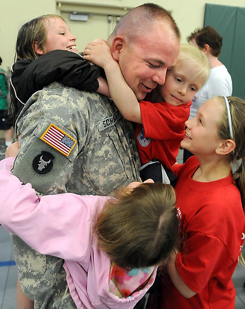 Minnesota National Guard Red Bull 34th Infantry Division soldier Dana Schiller is mobbed by his daughters (clockwise from back left) Sara, 9; Autumn, 5; Jadin, 11 and Malina, 6 after his return from the Middle East Friday at the Mankato National Guard Armory.