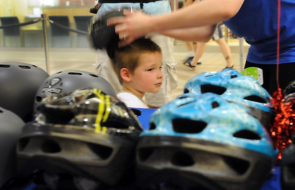 Braedon Siemers, 5, of St. Peter has a new helmet fitted to his head during the Mayo Clinic Health System Bike Safety Rally Thursday at the River Hills Mall.