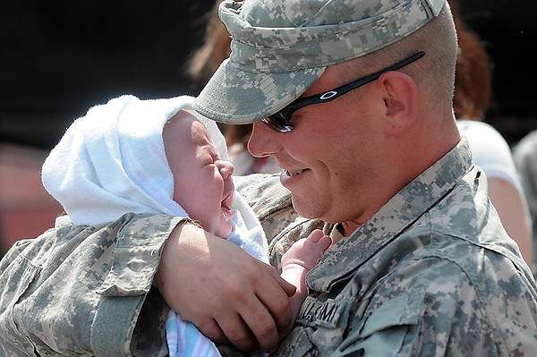 Anthony Risk embraces his three-month-old son, Jayden, after returning Tuesday from a year-long deployment to Kuwait with the Mankato-based 2nd Battalion 135th Infantry.