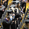 Graduates move their tassles during the second of three commencement ceremonies Saturday at Bresnan Arena.