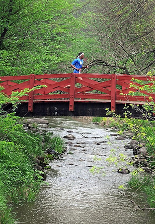 Devan Strowder, winner of the 5k race, crosses a bridge over Seven Mile Creek during the 7 at 7 trail race Saturday.