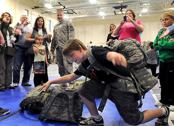 Tyler Harmon, 11, struggles to lift a backpack worn by his father, Red Bull 34th Infantry Division soldier Andrew Harmon (backround) after returning to Mankato from the Middle East Friday.
