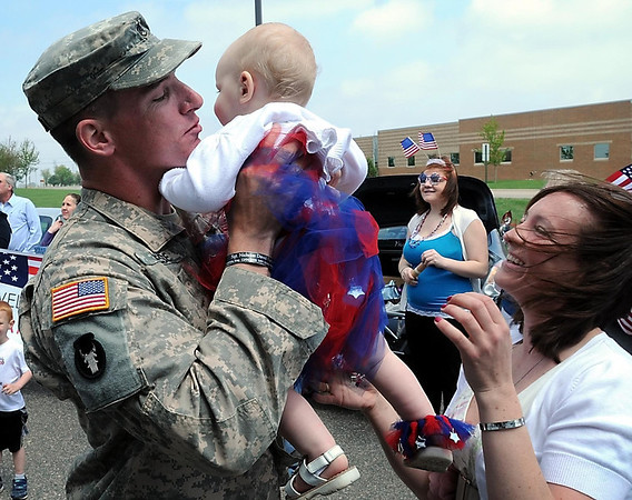 Returning National Guard member Tyler Neese reunites with Carie Wilson and their one-year-old daughter, Ella, Tuesday.