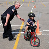 North Mankato Police reserve officer Jim Albright guides Avery Clifton, 5, through a bicycle safety course during the Mayo Clinic Health System Bike Safety Rally Thursday at the River Hills Mall.