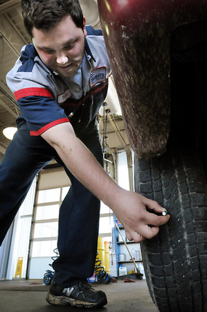 John Cross<br /> Tyler Ponozzo, a technician at Mankato Motors Company's Express Service, measures the depth of tread remaining on a tire, one of several safety-related items that are checked during routine oil changes.