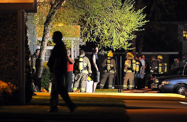 A man walks back into his apartment as North Mankato firefighters work on a fire in a neighboring apartment on Roe Crest Drive Tuesday night. No one was injured in the fire.