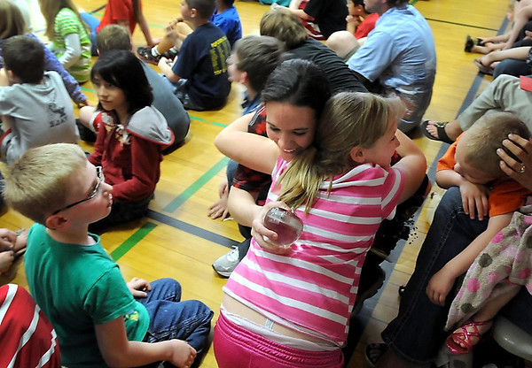 Roosevelt Elementary teacher Emily Seppmann gets a hug from Madison Dawley, one of her students, after receiving an award Friday afternoon at an assembly for being the 2012 WEM Outstanding Educator Award for Ethics in Education, which comes with $10,000.