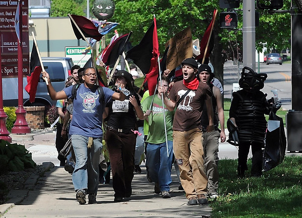 Occupy Mankato marchers shout as they pass by Rep. Tim Walz's office along Broad Street during a May Day march Tuesday.