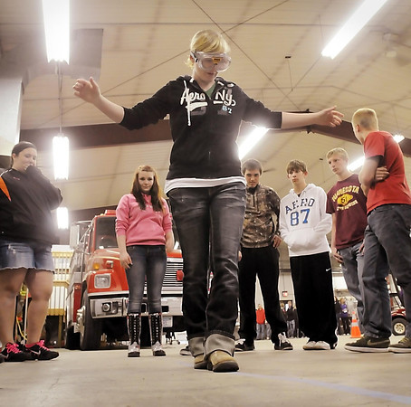Classmates watch as Cleveland High School senior Samantha Brunson attempts to walk a line while wearing glasses that simulate intoxication.