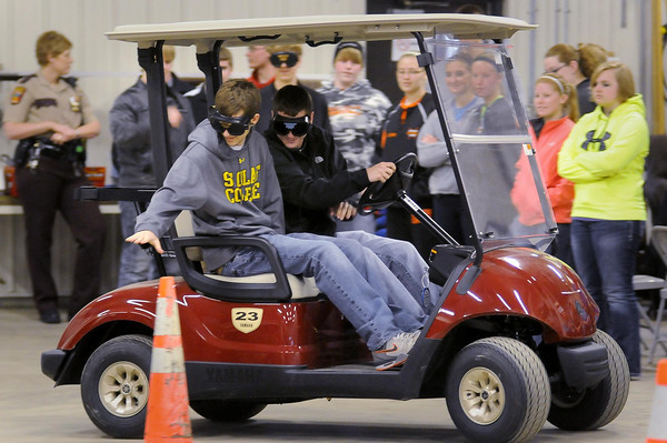 John Cross<br /> Cleveland High School seniors Mitchell Dummer (left) and Derek Ely negotiate a driving course in a golf cart while wearing glasses that simulate night-time driving while impaired. Students at the school were attending a Prom Safety Day sponsored by public safety organizations to remind students of the risks associated with alcohol consumption on prom night,  historically an event where youth might be tempted to imbibe.