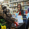 "John Cross<br /> Gustavus Adolphus College juniors Baileigh Faust (left) and Lacie Micek check out a dragon that was part of a floral arrangement to accompany J.R.R. Tolkien's book ""The Hobbit"" at Books In Bloom in the Folke Bernadotte Memorial Library."