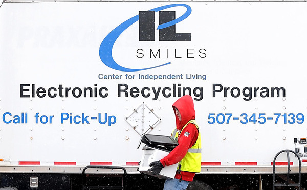 Pat Christman<br /> Jared Blackwell carries monitors and a microwave to be recycled during SMILES Center for Independent Living's 8th annual electronics recycling in the Madison East parking lot.