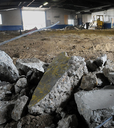 A bulldozer works on the floor of the former city bus garage that is being remodeled to be the home of the Children's Museum of Southern Minnesota. Photo by John Cross