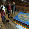 Visitors examine a completed mandala sand painting Wednesday afternoon at Christ Chapel at Gustavus Adolphus College. The mandala was created by Tibetan monks as part of the college's Mayday Conference and was destroyed during a ceremony Wednesday afternoon. Photo by Pat Christman