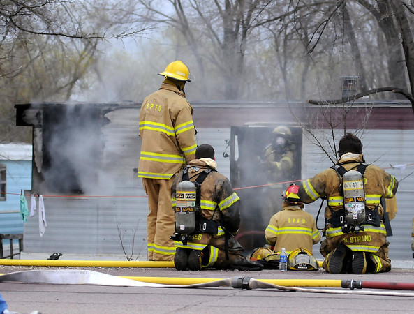 Fiirefighters extinguish a fire in a mobile home at a mobile home park on the north edge of St. Peter on Wednesday. Photo by John Cross