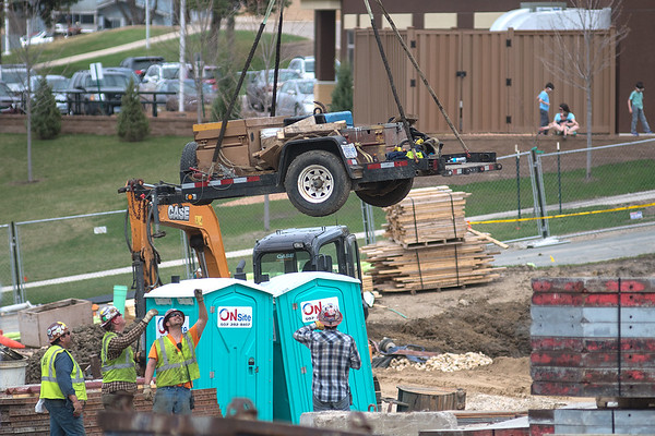 Construction workers at the Blue Earth County Government Center help a crane operator lower a trailer of equipment down to their work area on Thursday. Photo by Jackson Forderer