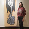 Gustavus senior Sara Blinn with her artwork titled Phi Krasue. Blinn said it is not a self-portrait, but said it looks a bit like her sister. Photo by Jackson Forderer