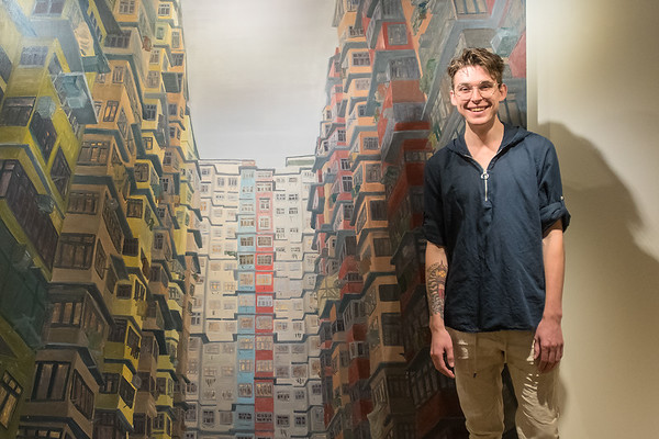 August Moehrke, a Gustavus senior, with his oil painting titled The Spirits of Yick Fat in the Hillstrom Museum of Art. Photo by Jackson Forderer