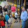 "John Cross<br /> From back left, Neil Baker of Eide Bailly, Doug Mulder of CAB Construction, Tom Kammer of South Central College, Matt Schindle of Dotson Iron Foundry, Sarah Richards of Jones Metal Products, Joe Bohrer of Ameristar Manufacturing and Mitch Jacobs of V-Tech watch as youngsters from Monroe Elementary School board a bus bound for the Children's Museum, Thursday. Their businesses made donations that allowed 800 students from area grade schools to travel to St. Paul to view ""How People Make Things Work"" at the museum."