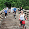Bicyclists and walkers gather to recreate a photo from 1911 on the Red Jacket trestle Saturday.