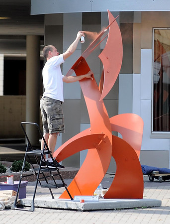 "Artist Matt Miller puts some finishing touches on ""Chasing My Tail Again"" Saturday morning."