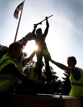 "Volunteers raise a sculpture titled ""Giving Thanks,"" of a Native American warrior praying with his pipe, near the Verizon Wireless Center Saturday while installing new sculptures on the CityArt Walking Sculpture Tour."