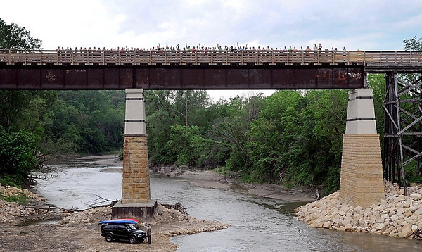 Walkers and bikers recreate a famous 1911 photo of the Red Jacket trestle, minus the original car bridge, during Saturday's re-opening celebration.