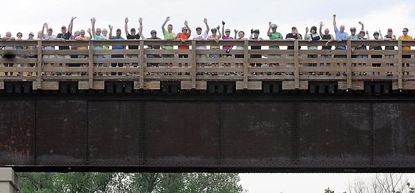 Bikers and walkers wave from the Red Jacket trestle as they have their picture taken Saturday.