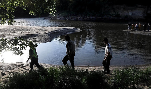 Emergency personnel walk along the bank of the Blue Earth River as divers search for a tuber lost in the river Tuesday afternoon near the Rapidan Dam Park campground.