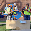 "Volunteers move ""Aplomb"" into position while installing sculptures Saturday morning."