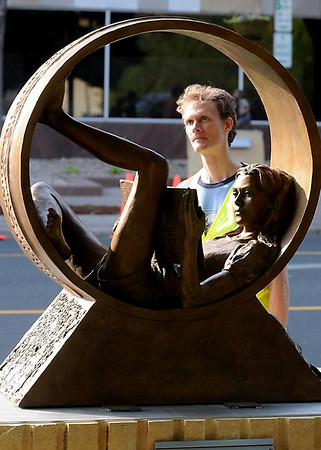 """Volunteer Matt Borowy examines Karen Crain's """"Circle of Friends"""" during the installation of new sculptures on the CityArt Walking Sculpture Tour Saturday morning in Mankato. Crain also had a piece in last years tour, titled """"Spirit of Energy."""""""