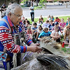 "John Cross<br /> David Larsen dons articles of ceremonial Dakota garb for students from Monroe Elementary School as part of a program ""Who Are the Dakota"" Tuesday at Reconciliation Park."