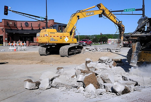 .John Cross<br /> City crews jackhammer damaged panels of concrete at the intersection of South Front Street and Cherry Street Monday after a Saturday water main break undermined them. It is hoped the intersection can be opened to traffic again by the weekend.