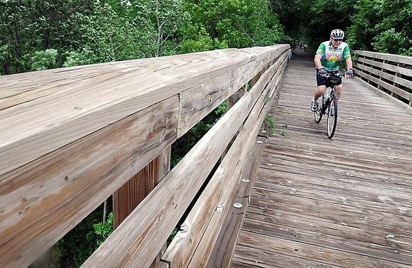 A bicycle rider cruises along on the Red Jacket Trail's trestle bridge during a celebration of the reopening of the historic trestle Saturday.