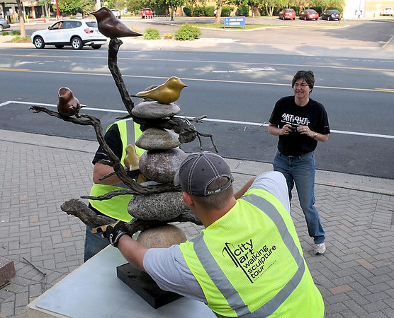 Artist Deb Zelenak watches as volunteers place her sculpture on the CityArt Walking Sculpture Tour Saturday morning in downtown Mankato.