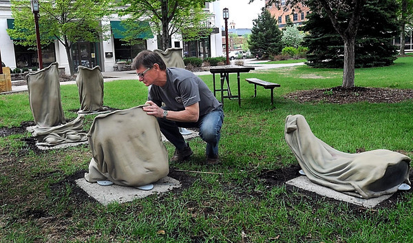"""Pat Christman<br /> Artist Roger Golden of Toronto arranges parts of his sculpture, entitled """"Sack Race,"""" during its installation on the CityArt Walking Sculpture Tour in Mankato."""