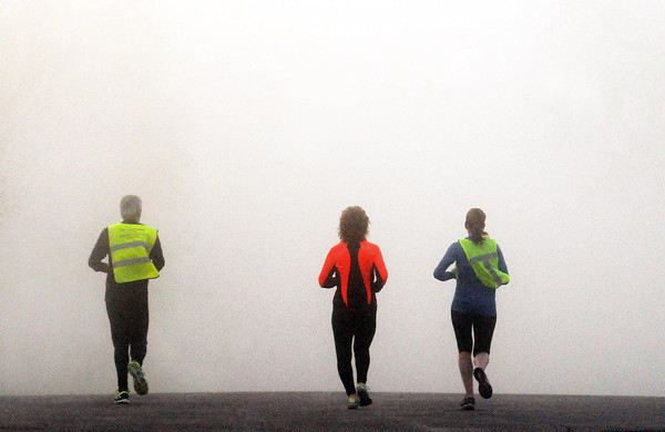 Morning joggers on a St. Peter street head into the thick fog that enveloped much of the area on Tuesday morniing.<br /> Photo by John Cross
