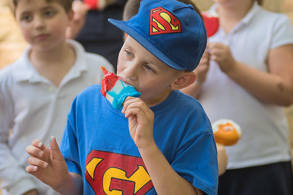 After handing out Dilly Bars to elementary students at Mankato Loyola, Gabe Speckel, 7, enjoys his own Dairy Queen treat with his classmates on the playground on Thursday. Photo by Jackson Forderer