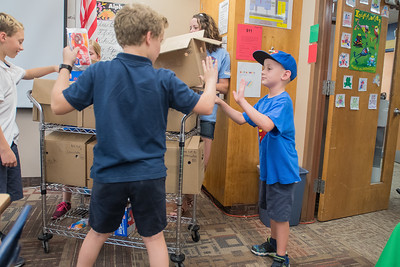 Gabe Speckel (right), 7, gets a high five from a fellow student at Mankato Loyola as he handed out Dilly Bars with his sister Amelia Speckel, to classrooms at the school on Thursday. Gabe is celebrating one year after having a kidney transplant. Photo by Jackson Forderer