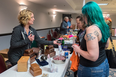 Wendy June (left) shows Nicole Richards (right) and Shelly Wingen an urn for a pet at a Pheasants Forever event at the Kato Entertainment Center. June has started the business Mankato Pet Cremation out of her home and wants to serve the greater Mankato area. Photo by Jackson Forderer