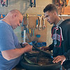 Volunteer John Zarn (left) helps Isaiah Kessel put a new tube onto his bike tire at Key City Bike on Tuesday. The nonprofit is available for people to make repairs to their bike with help from volunteers. Photo by Jackson Forderer