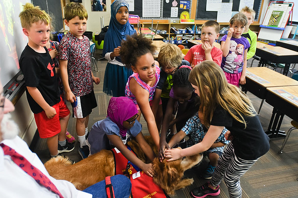 Roosevelt Elementary students pet Walter Roberts'  two therapy dogs Prairie and Murphy. Roberts was at the school for career day and he will be retiring next month after 24 years of teaching at Minnesota State. Photo by Jackson Forderer