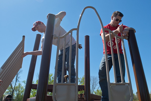 Tripp Hudson (left) and Cody Vanasse work on assembling a section of a playground on Saturday at the new Southview Park. Volunteers from the neighborhood, Target and Minnesota State pitched in to put up the playground at the intersection of Stoltzman Road and Catalina Drive. Photo by Jackson Forderer