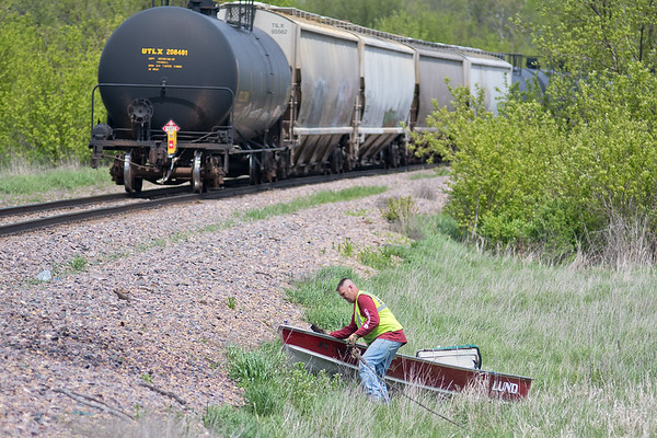 Matt Maloney of Maloney Enterprises hooks up a wench to a boat owned by Gerald Lee after it was struck by a train at the intersection of County Road 113 and 155 in rural Lake Crystal. Lee said he didn't see the train until the last second. There were no injuries in the collision. Photo by Jackson Forderer